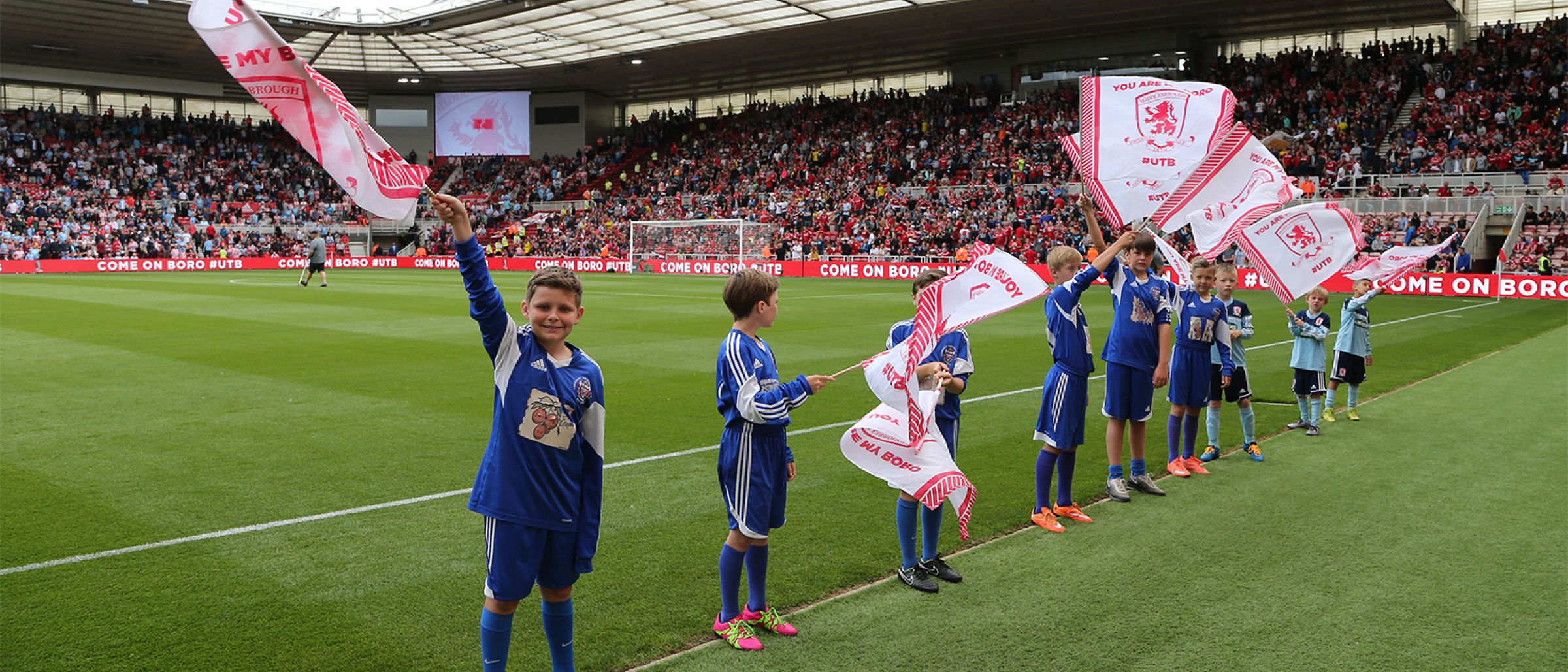 Young fans waves flags pitchside as part of the Matchday Squad scheme