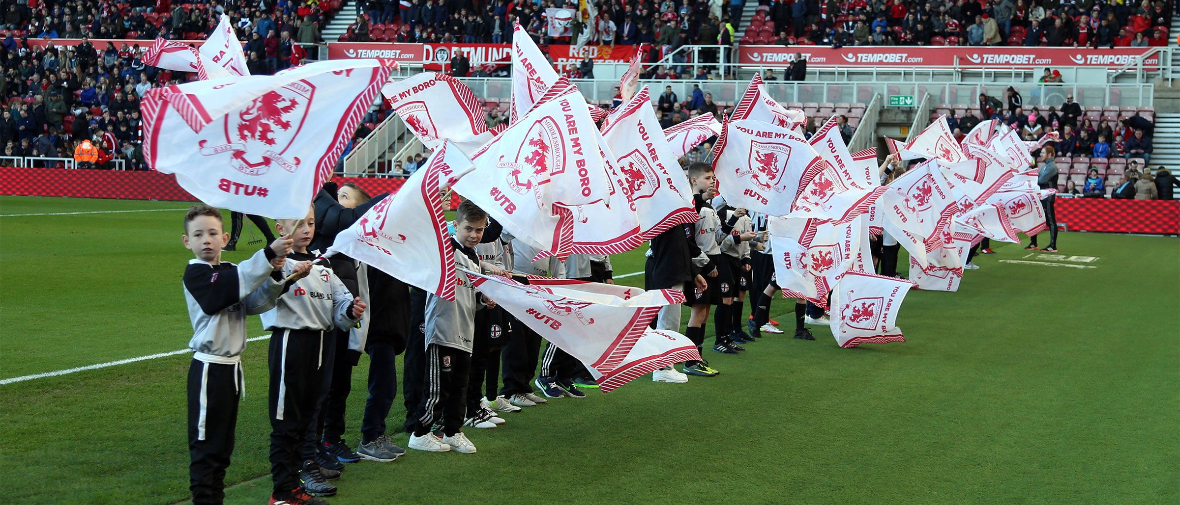 Kids in the Matchday Squad scheme wave flags pitchside