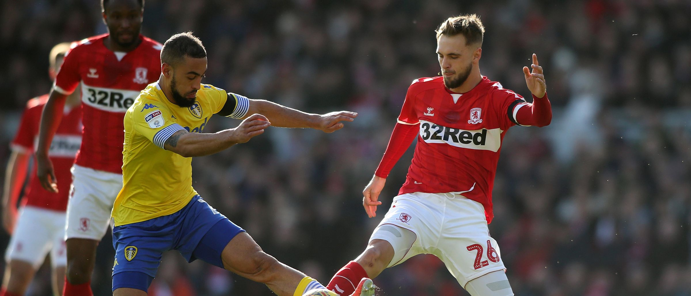 Lewis Wing competes with Leeds' Kemar Roofe for the ball